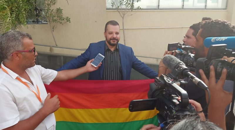 Mounir Baatour donnant une conférence de presse au siège de son parti avec la bannière LGBTQ