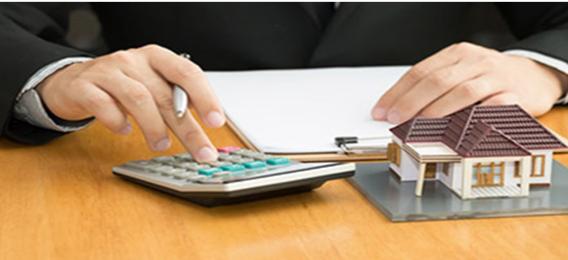 Un homme calculant son impôt sur la fortune immobilière (IFI)