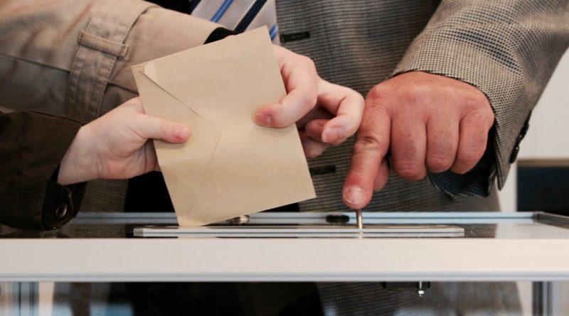 Une personne glissant son bulletin de vote dans l'urne