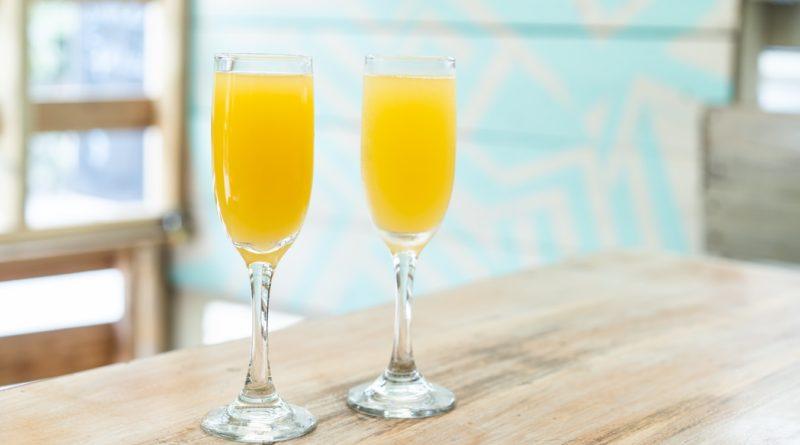 Deux verres de jus d'orang posés sur une table.