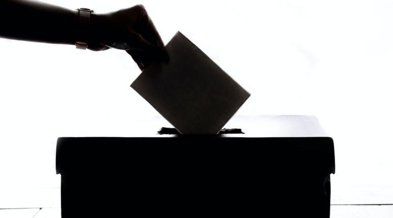 Une personne glissant son bulletin de vote dans une urne.