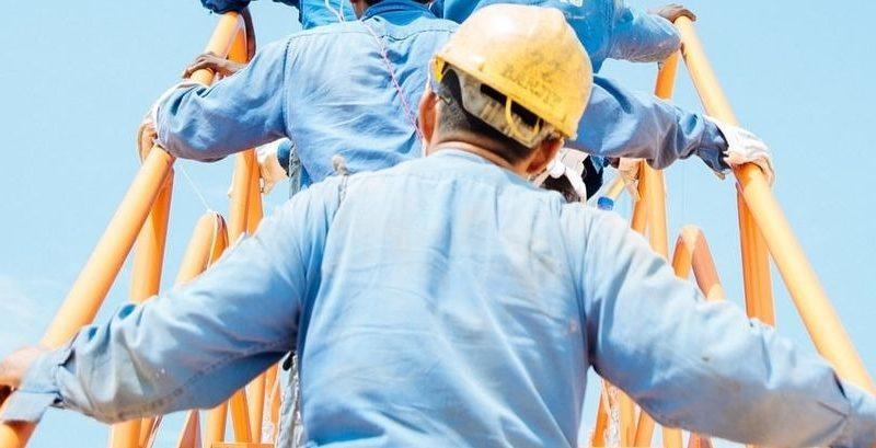 Des ouvriers du bâtiment escaladant une échelle.