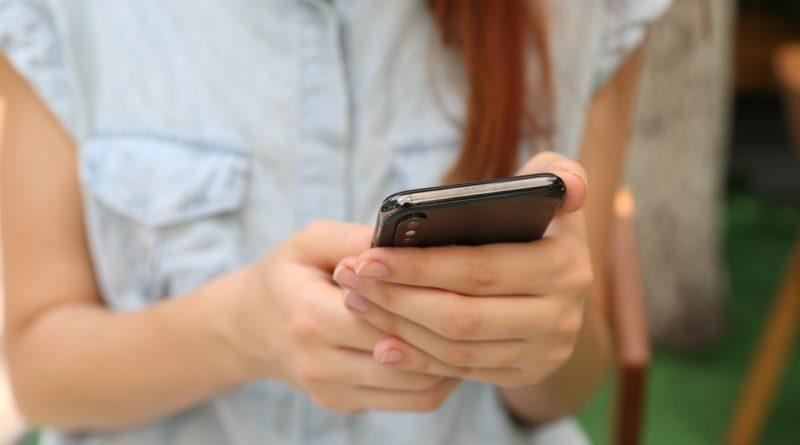 Une jeune femme manipulant son smartphone (Photo : Unsplash).
