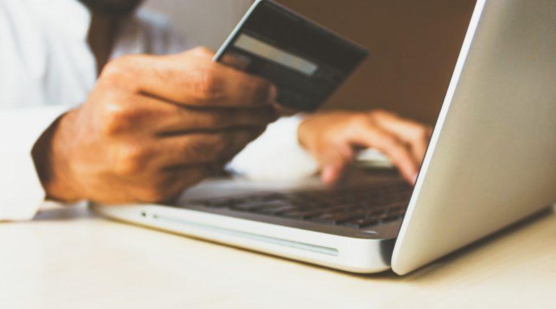 Un homme effectuant des achats à partir de son ordinateur avec sa carte bancaire.